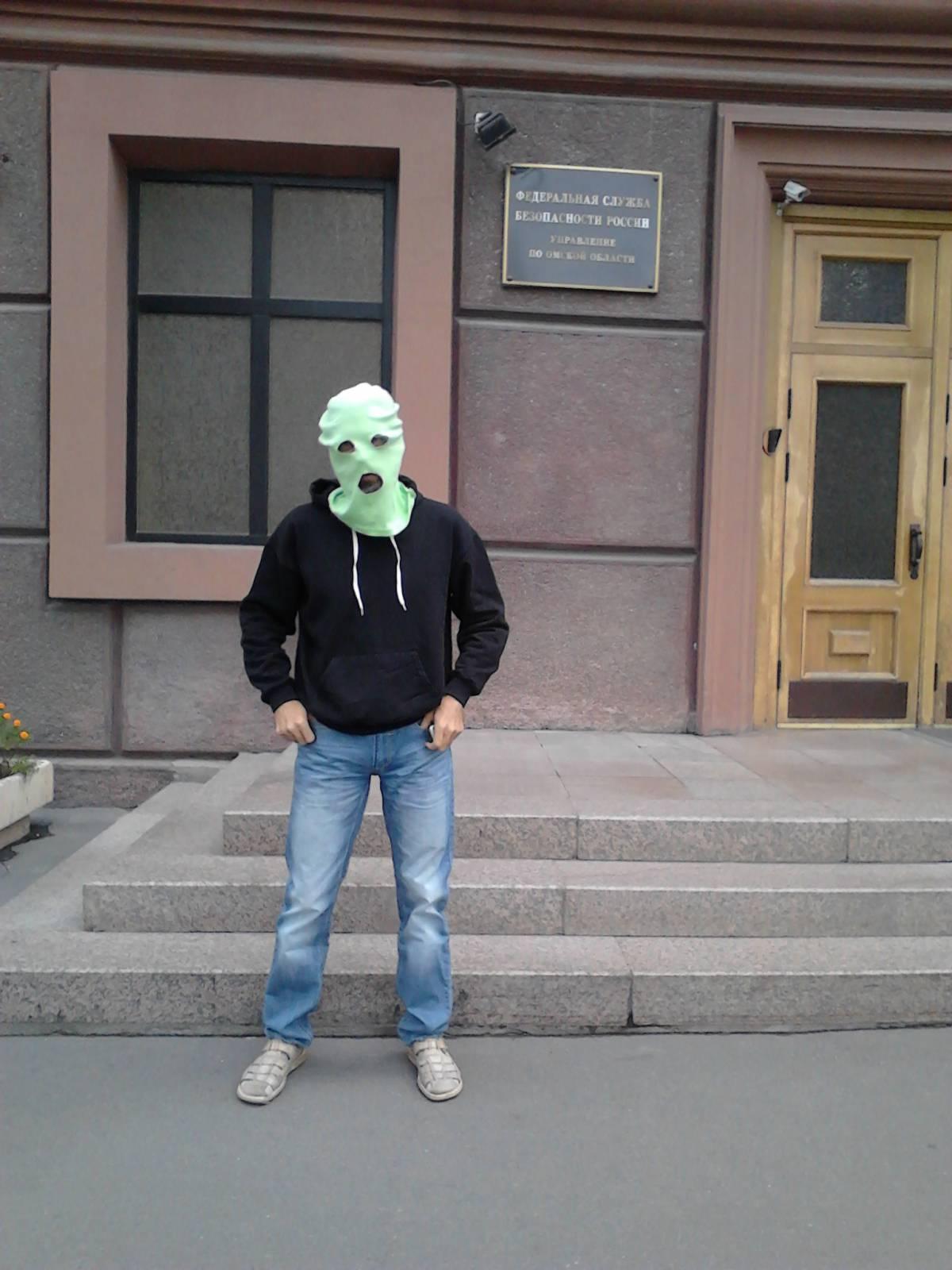 Виктор Корб в балаклаве на фоне вывески УФСБ по Омской области